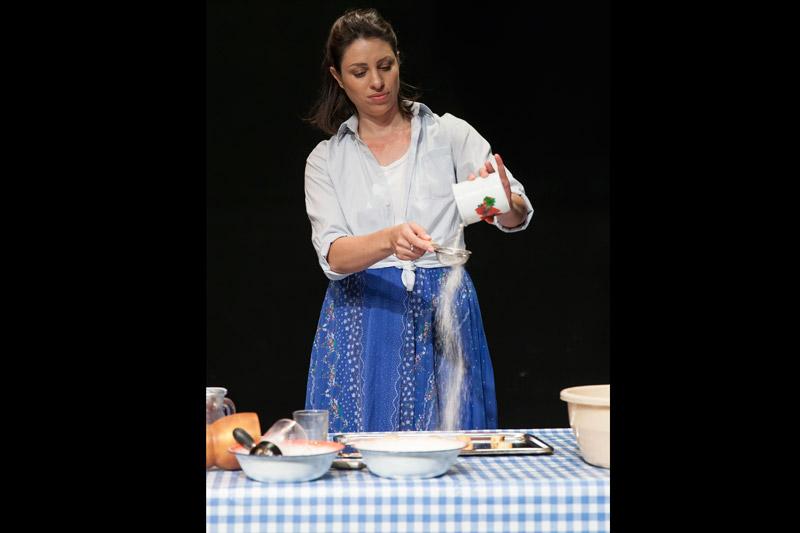 השחקנית עומדת מאחורי השולחן ומסננת קמח לתבנית