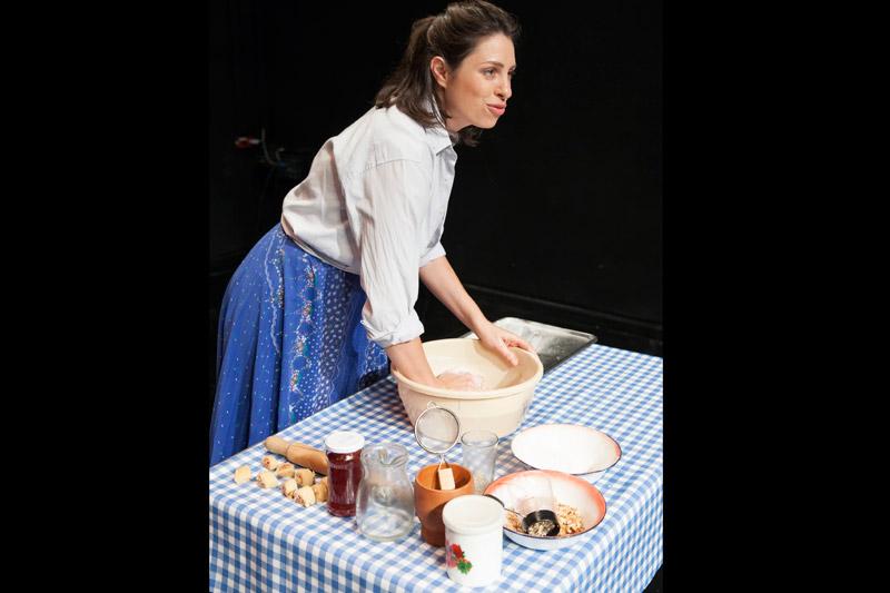 השחקנית עומדת מאחורי השולחן ולשה בצק בתוך קערה