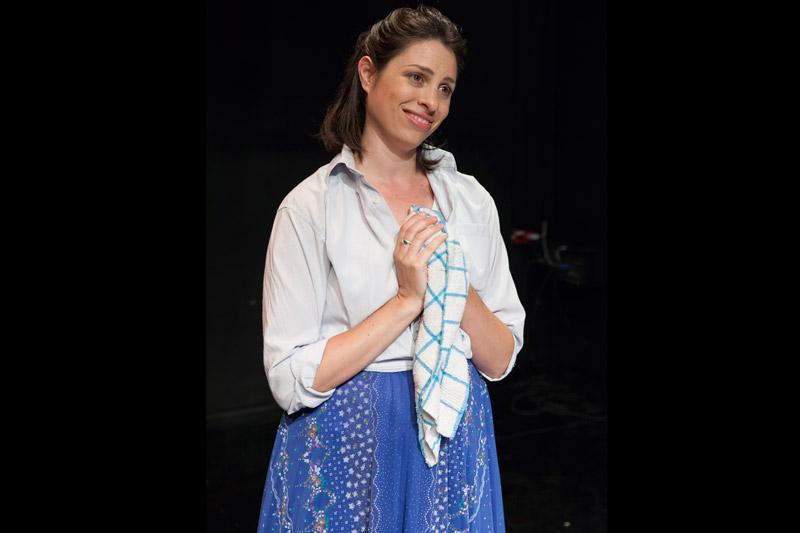 השחקנית עומדת ומחייכת ומשלבת ידיים