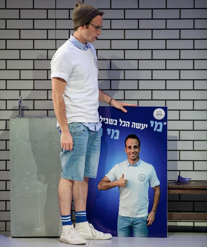 מיכאל עומד ומחזיק שלט