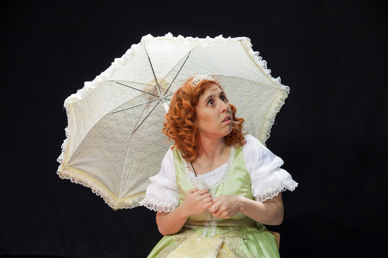 הנסיכה יושבת ומחזיקה מטרייה