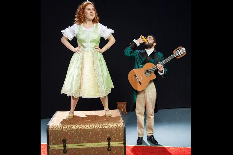 הנסיכה עומדת על התיבה עם ידיים על המותניים, משרתה מאחוריה מחזיק בגיטרה