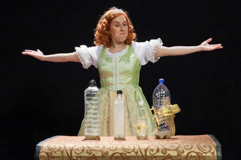 הנסיכה עומדת מאחורי התיבה ומושיטה ידיים, על התיבה עומדים ארבעה בקבוקים