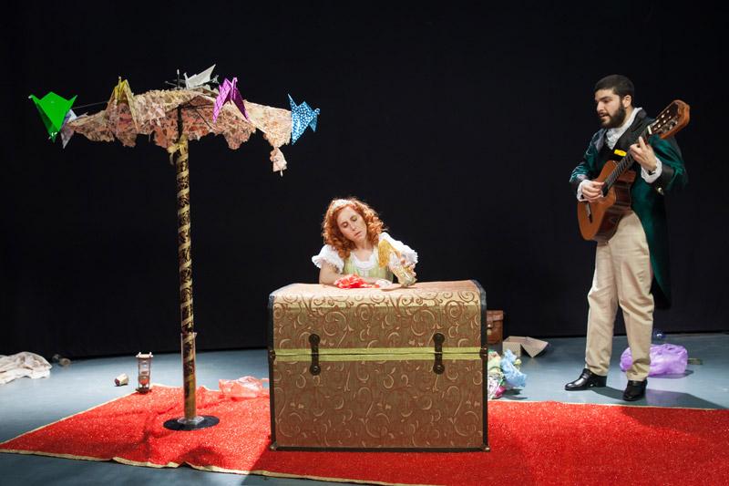 הנסיכה נשענת על התיבה והמשרת עומד ליד עם הגיטרה ביד