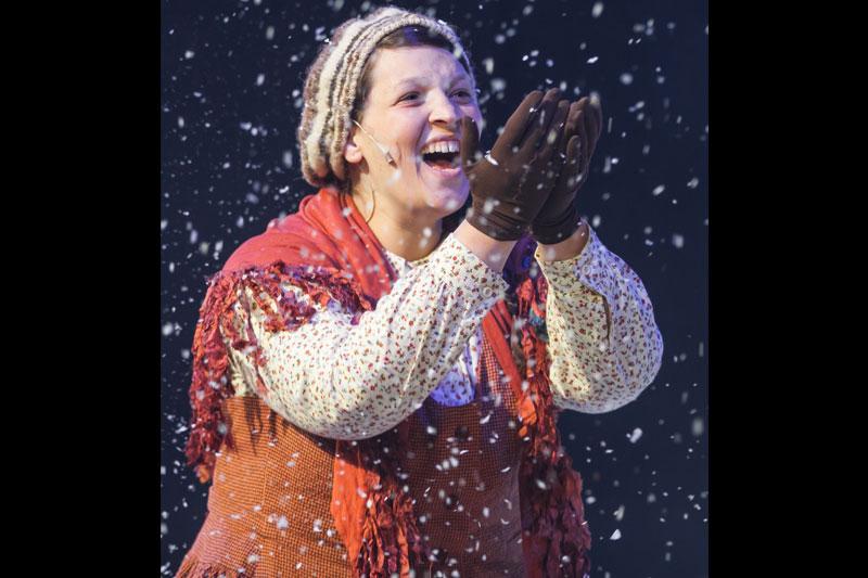 גרדה עומדת שמחה ותופסת את השלג בידיה