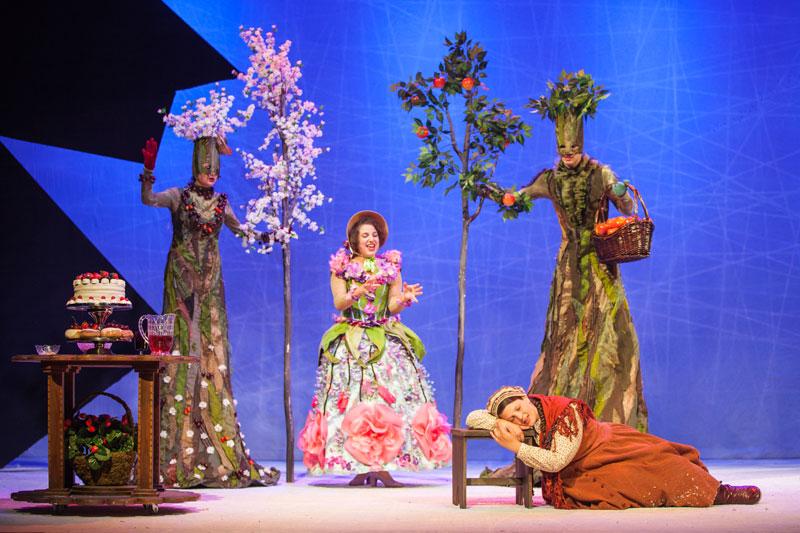 גרדה נחה על הכסא ומאחוריה מלכת הפרחים ושני עצים