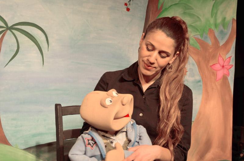 הבובה יושבת על השחקנית והם מסתכלים אחד על השני