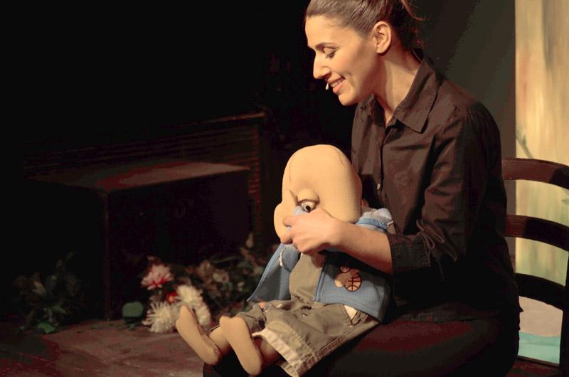 השחקנית מפעילה את הבובה שיושבת עליה