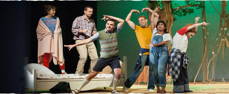 שישה שחקנים הרוקדים ליד מיטה
