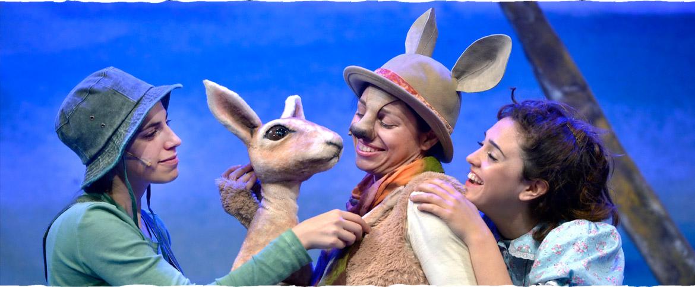 """צילום מתוך ההצגה """"דוט והקנגורו"""" - דמות מחופשת לקנגורו, דמות ילדה וילד ובובת קנגורו קטנה"""