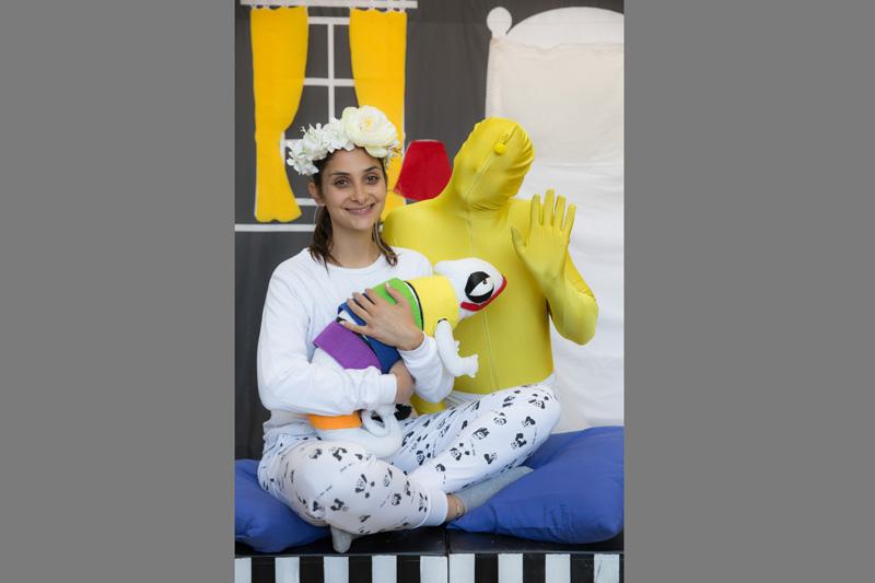 הילדה יושבת ומחבקת את הבובה זיקית שלה ומאחוריה דמות צהובה מרימה יד לשלום