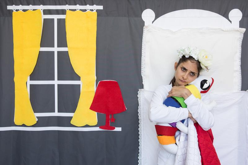 הילדה שוכבת במיטה עצובה ומחבקת את הבובה זיקית שלה