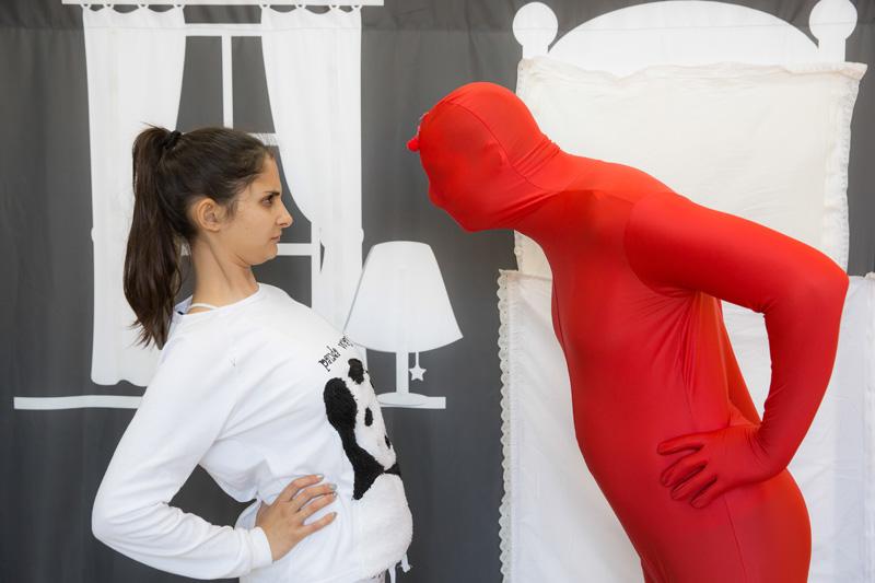 הדמות האדומה והילדה מסתכלים אחד על השני בהפתעה