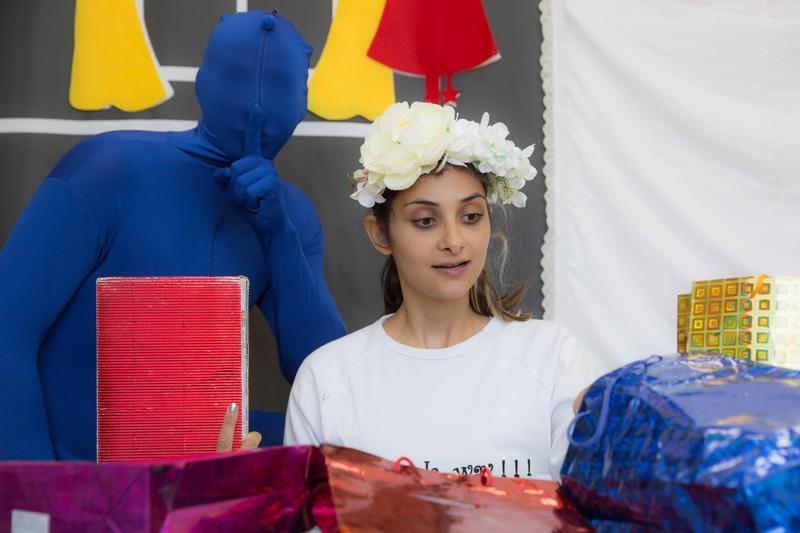 הילדה עומדת מופתעת מול מתנות ומאחוריה דמות בצבע כחול מסמנת שקט עם האצבע