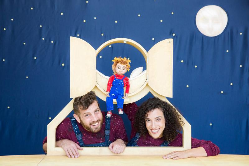 שתי הדמויות מסתכלים דרך מסגרת עץ ומעליהם יושבת בובה