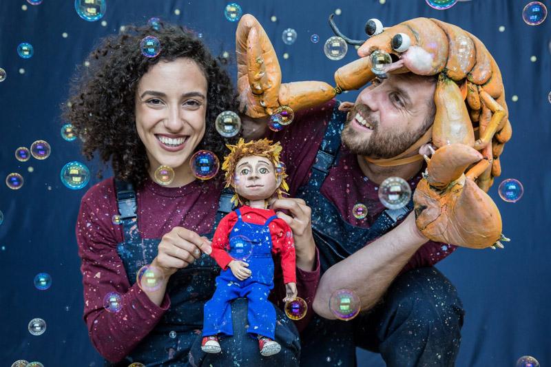 שתי הדמויות מחזיקים את הבובה. על הראש של דמות אחת יש בובה של סרטן